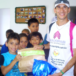 Young children receive gym shoes donated by members from Cia Athletica clubs in Brazil