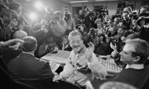 "Eddie ""The Eagle"" Edwards waves to a large group of journalists during a press briefing"