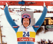 "Eddie ""The Eagle"" Edwards holds his skis above his head"