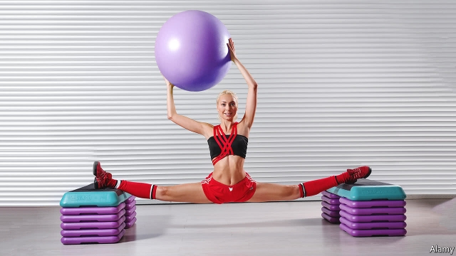 White women holding a large Swiss Ball above her head while doing the splits